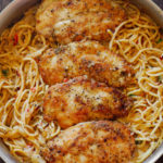Chicken breasts on spaghetti in a pan