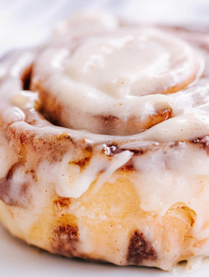 Cinnamon Roll with white frosting close up on white background