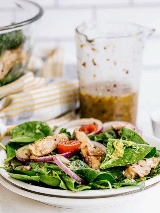 Dijon Mustard Chicken Salad on a white plate with Dijon Mustard Dressing in a glass